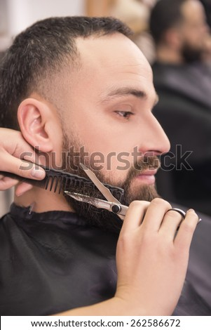 Hairdresser shaving  with scissors and combs of satisfied client in professional hairdressing salon. - stock photo