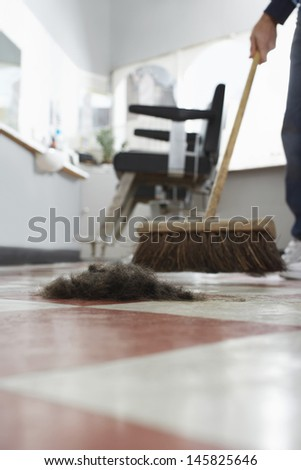 Hairdresser sweeping hair clippings on floor in barber shop - stock photo
