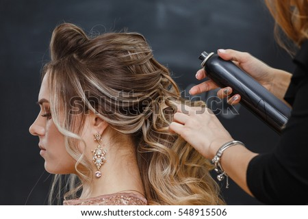 Hairdresser using hairspray on client's hair at salon