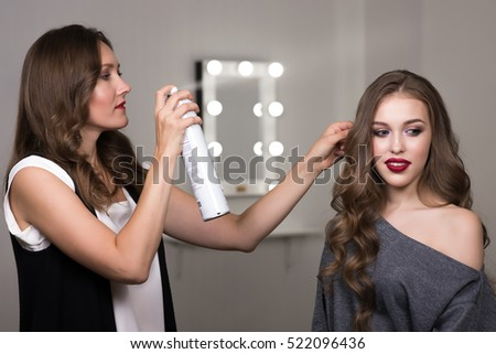 Hairdresser using hairspray on client's hair at salon, two beautiful women