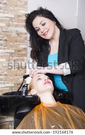 Hairdresser washes blonde hair - stock photo