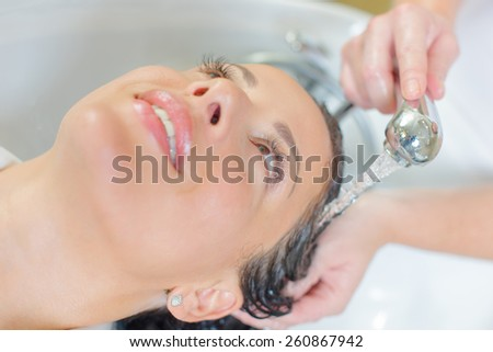 Hairdresser washing a woman's hair