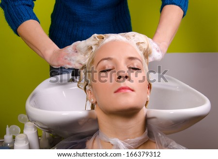 Hairdresser washing blond haired woman in the barber shop. - stock photo