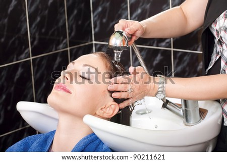 Hairdresser washing hair of customer - stock photo