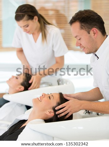 Hairdresser washing woman hair at the beauty salon - stock photo