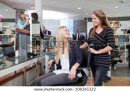 Hairdresser welcoming customer to beauty salon