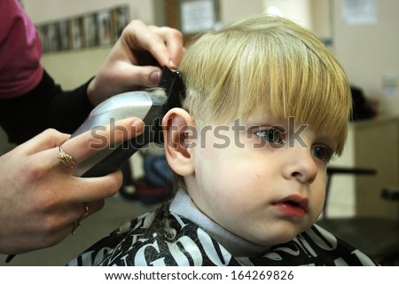 Hairdresser working with boy's haircut  - stock photo