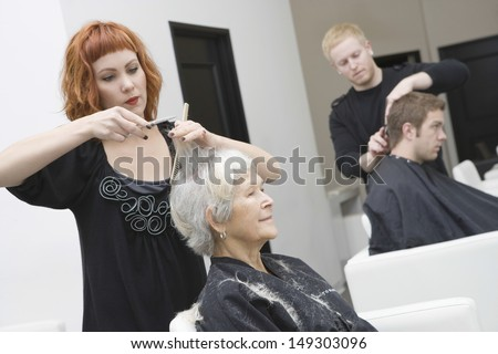 Hairdressers giving haircut to customers in unisex salon - stock photo
