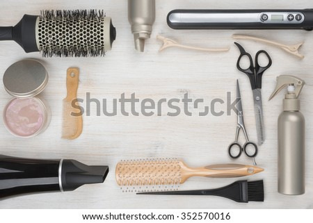 Hairdressing tools on wooden background with copyspace in the middle - stock photo