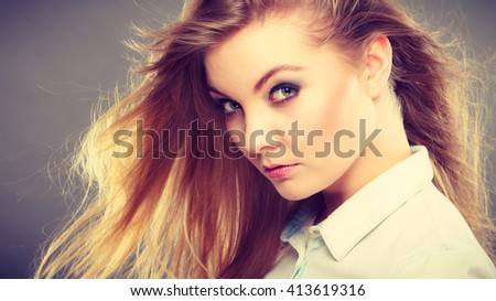 Hairstyle and haircare concept. Portrait of blonde charming attractive young lady with open waving hair. Woman with healthy and beauty hairdo coiffure.