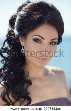 Hairstyle. Makeup. Brunette attractive woman with eye make-up, long wavy and curly hair styles.
