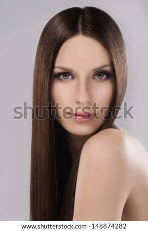 Hairstyle. Portrait of thoughtful young women with beautiful hair looking at camera while isolated on grey - stock photo