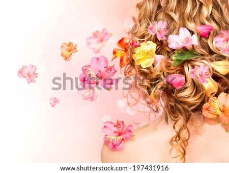 Hairstyle with colorful flowers. Beautiful healthy curly hair decorated with flowers.Over blurred pink background. Hair care concept. Backside view. Long permed hair style - stock photo