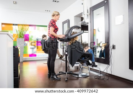 Hairstylist Adjusting Drying Accelerator Over Customer's Head