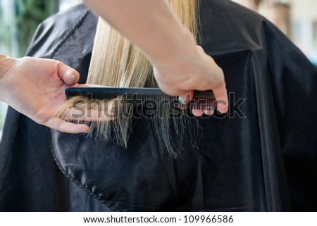 Hairstylist combing hair of a blonde female customer before haircut at salon