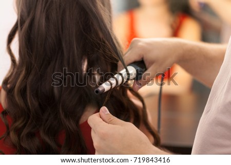 Hairstylist curling hair client in hairdressing salon