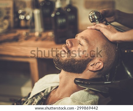 Hairstylist washing client's hair in barber shop - stock photo