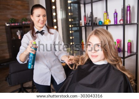 Hairstylist with hairspray and female client - stock photo