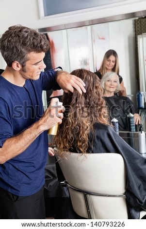 Hairstylists setting up female customer's hair at beauty parlor - stock photo