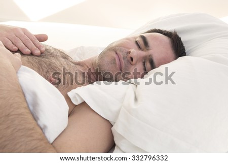 hairy shirtless man is sleeping in bed - stock photo
