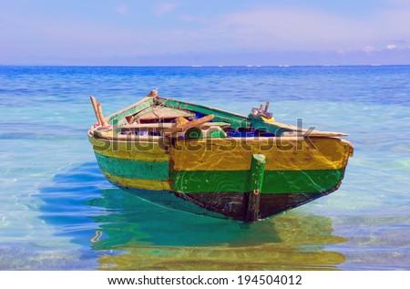 Haitian Fishing Boat: an old fishing boat docked near Labadee, Haiti. - stock photo
