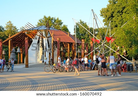 HAJDUSZOBOSZLO, HUNGARY - JULY 23: Tourists visit the center of Hajduszoboszlo, Hungary on July 23, 2013. Hajduszoboszlo is a popular spa resort in Hungary. It is located 202 km east of Budapest. - stock photo