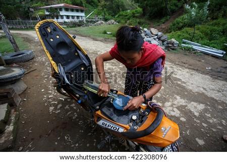 HAKHA, MYANMAR - JUNE 19 2015: Local woman filling petrol in the Hakha region in Chin State, Myanmar. - stock photo