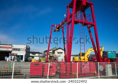 HAKONE, JAPAN - DECEMBER 3, 2014: A crane at an industrial lot loads mobile generators for local use and for export. Small and medium industry make a substantial contribution to the economy of Japan. - stock photo