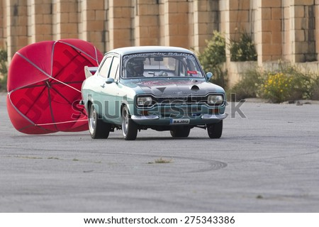 Hal Far, Malta May 2, 2015: Heavily modified Ford Escort Mk I used as dragsters doing some practice runs at the EX-RAF airfield runway. - stock photo