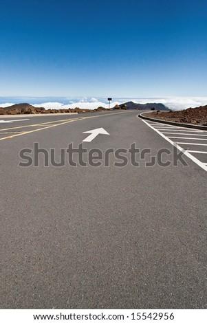 Haleakala Summit road with arrow pointing to clouds on horizon - stock photo
