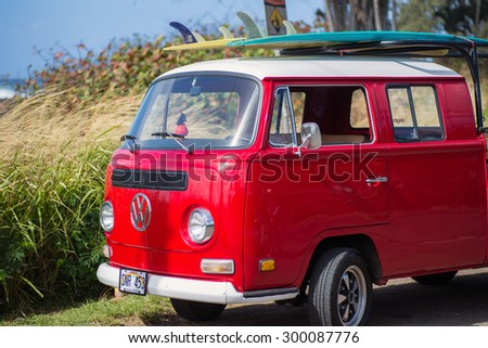 HALEIWA, HAWAII - FEB 10:  Classic red volkswagon van with surfboards on rack on top on sunny day in Haleiwa, Hawaii on February 10, 2015.  Haleiwa is known for its big waves in the winter season. - stock photo