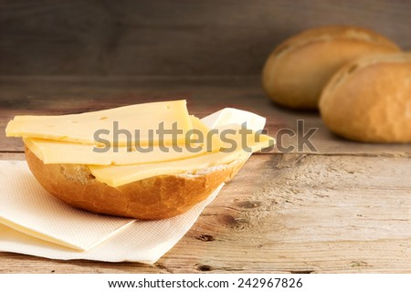 half a bun with cheese and blurry bread rolls in the background on old wood - stock photo
