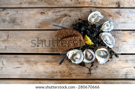 Half a dozen of fresh oysters decorated with lemon and slices of bread in a plate on a wooden table - stock photo