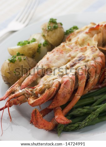 Half a Lobster Thermidor with New Potatoes and Asparagus Spears - stock photo