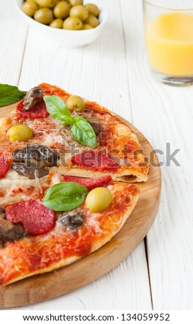 half a pizza with salami and sliced �¢??�¢??mushrooms, closeup fast food