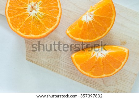 Half and two slices of fresh oranges fruit on a wooden chopping block on white background. Top view
