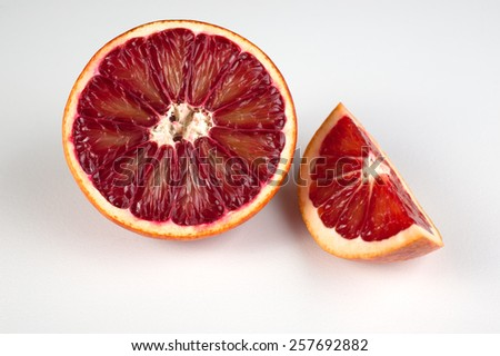 half and wedge of  red blood sicilian orange isolated on white  - stock photo