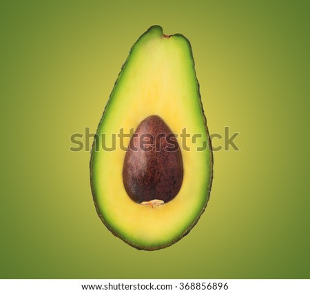 Half avocado with stone isolated on green background - stock photo