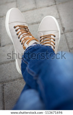 Half body of a male teenager, posing he jeans and sneakers, sitting cross foot - stock photo