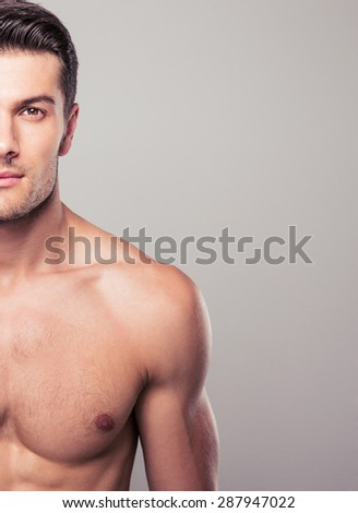 Half body portrait of a handsome man over gray background. Looking at camera - stock photo