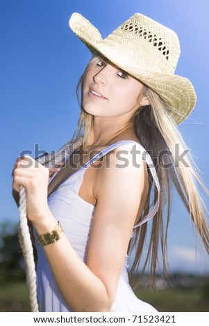 Half Body Portrait Of Attractive Young Woman With Rope And Cowboy Hat In Countryside Blue Sky Background - stock photo
