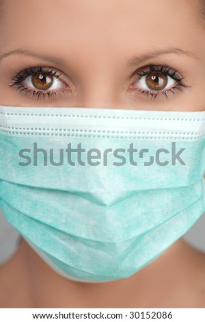 Half body portrait of young woman wearing protective medical face mask, studio background.