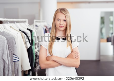 Half Body Shot of a Confident Blond Young Woman Looking at the Camera with Arms Crossing on her Chest Inside the Clothing Store. - stock photo