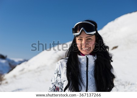 Half Body Shot of a Pretty Female Skier Smiling at the Camera Against Mountain Filled with Snow.