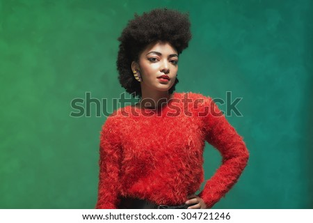 Half body Shot of a Stylish Young Woman with Afro Hair, Wearing Furry Red Shirt and Black Shorts, Looking at the Camera Against Green Wall - stock photo