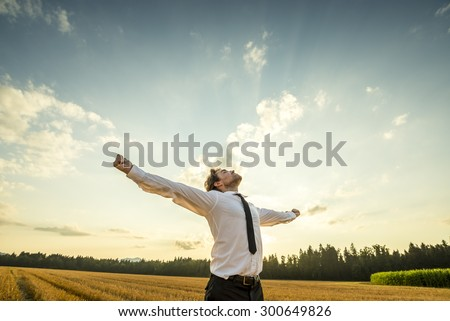 Half Body Shot of a Thankful Young Businessman Looking up the Sky with Wide Open Arms, Standing at the Open Field. - stock photo