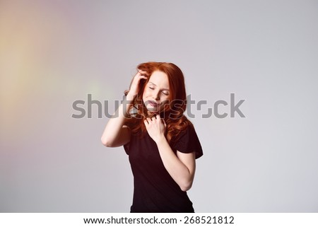 Half Body Shot of a Thoughtful Young Woman in Casual Black Shirt Holding her Long Red Hair with eyes Closed. Captured in Studio with Gray Background and Light Coming From the Left. - stock photo