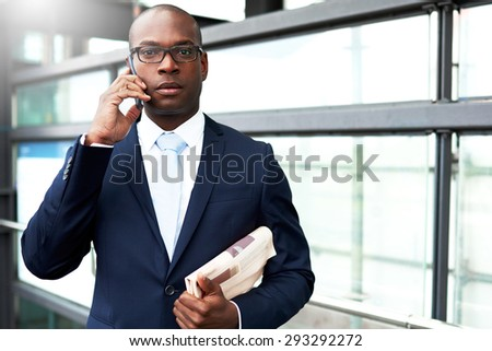 Half Body Shot of a Young African-American Businessman Calling on Mobile Phone While Holding a Newspaper, Looking at the Camera - stock photo