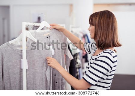 Half Body Shot of a Young Woman Looking for Casual Shirt with Good Quality Hanged on Rail Inside a Clothing Store - stock photo