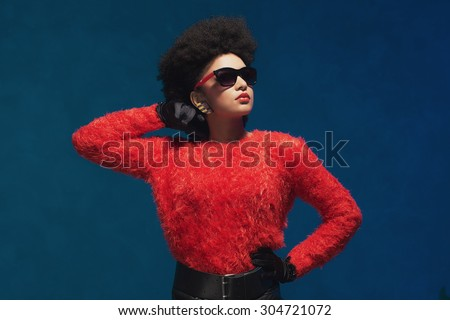 Half body shot of a young woman with Afro hair, posing in fashionable attire with sunglasses against blue wall background. - stock photo